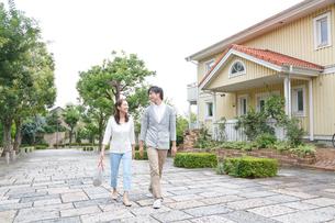 新緑の住宅街を歩く若いカップルの写真素材 [FYI02824632]