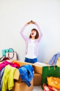 箱から出る服や鞄などが散らかった部屋と財布を持つ女性の写真素材 [FYI02824644]