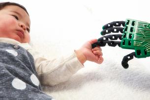 ロボットの手を握る赤ちゃんの写真素材 [FYI02824680]