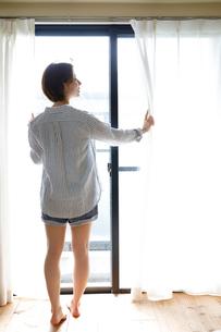 窓辺に佇む後姿の女性の写真素材 [FYI02824700]