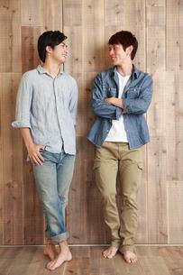 木の壁の前で微笑む若い男性2人の写真素材 [FYI02824702]