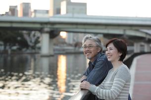 夕暮れの川辺に佇むミドル夫婦の写真素材 [FYI02824706]