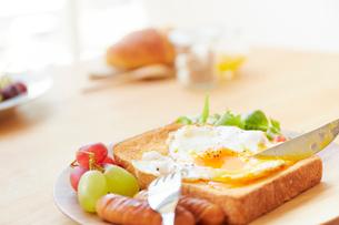 食パンの上に置かれた目玉焼きの黄身部分にナイフを入れる様子の写真素材 [FYI02824708]