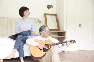 ギターを弾くミドル男性と読書をするミドル女性の写真素材 [FYI02824709]
