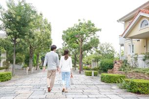 新緑の住宅街を歩く後姿の若いカップルの写真素材 [FYI02824712]