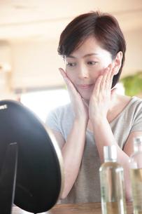 頬に手を当て鏡を見るミドル女性の写真素材 [FYI02824719]