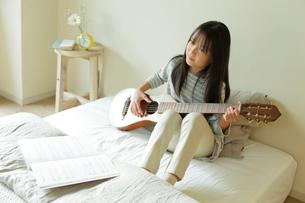 ベッドでギターを持つ少女の写真素材 [FYI02824739]