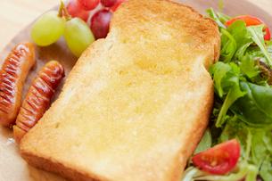 ダイニングテーブルの上の皿に盛りつけられた朝食セットの写真素材 [FYI02824748]