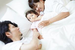 ベッドの上に並んで寝そべる赤ちゃんと両親の写真素材 [FYI02824755]