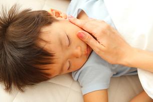 眠る男の子の頬に触れる母親の手の写真素材 [FYI02824769]