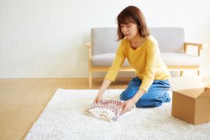 セーターをたたんで出荷作業をする女性の写真素材 [FYI02824772]
