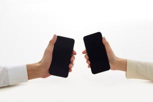 新しいスマートフォンを持つ二人の手の写真素材 [FYI02824783]