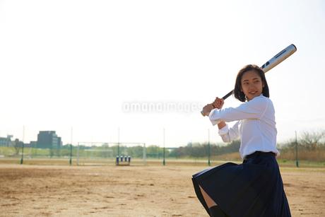 グラウンドで野球のバットを振る女子高生の写真素材 [FYI02824790]