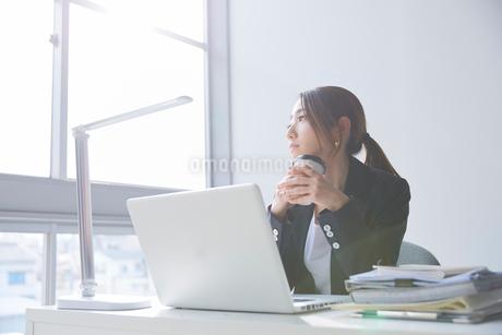 職場のデスクで窓の外を見て暗い表情をする女性の写真素材 [FYI02824812]