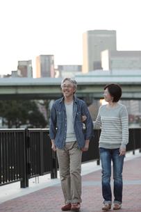 夕暮れの川辺を散歩するミドル夫婦の写真素材 [FYI02824815]
