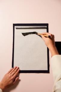 薄いピンクの背景の書道をする女性の手の写真素材 [FYI02824834]