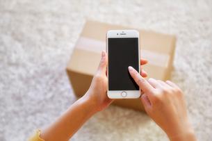 荷物の前でスマートフォンを操作する女性の手元の写真素材 [FYI02824835]