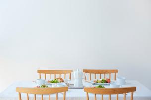 ダイニングテーブルの上に置かれた四人分の食事プレートの写真素材 [FYI02824836]