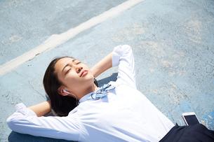 屋上でイヤホンで音楽を聴きながら寝る女子高生の写真素材 [FYI02824849]