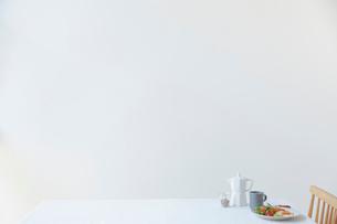 白い壁の前のダイニングテーブルに置かれた朝食セットの写真素材 [FYI02824854]