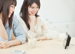 デジタルフォトフレームを見る2人の20代女性の写真素材 [FYI02824859]