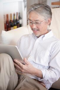 タブレットPCを見るミドル男性の写真素材 [FYI02824880]