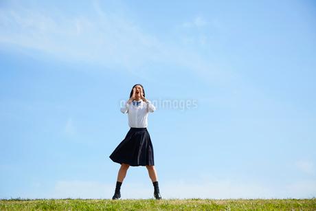 河川敷に立って叫ぶ女子高生の写真素材 [FYI02824885]