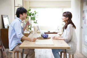 テーブルでお茶を飲む若いカップルの写真素材 [FYI02824894]