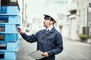 パレットを見ながら作業する男性の写真素材 [FYI02824909]