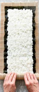 コンクリ調の天板上で巻き寿司を巻いている女性の写真素材 [FYI02824921]
