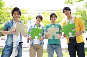 パズルピースを持つ4人の若い男性の写真素材 [FYI02824940]