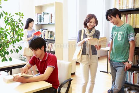 図書室で本を見る4人の男女大学生の写真素材 [FYI02824955]