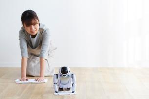 ロボットと雑巾掛けをする女性の写真素材 [FYI02824958]
