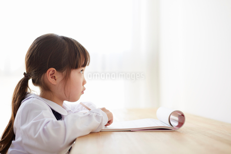 机で勉強をする小学生の女の子の写真素材 [FYI02824966]
