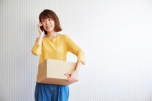 壁の前で荷物を持って電話をする女性の写真素材 [FYI02824979]