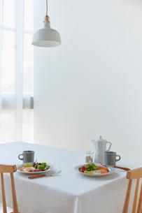 白い壁の前のダイニングテーブルに置かれた朝食セットの写真素材 [FYI02824983]
