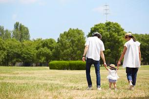 芝生の上を並んで歩く赤ちゃんと両親の写真素材 [FYI02824984]