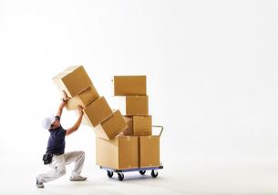 白バックの空間で台車の荷物を落としかけて抑える作業着の男性の写真素材 [FYI02824987]