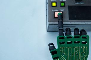 機械のボタンを押すロボットの手の写真素材 [FYI02824993]