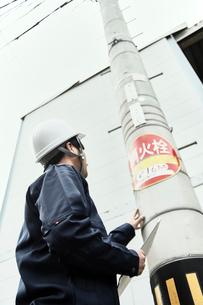 電柱に向かう作業服の男性の写真素材 [FYI02824995]