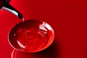 赤い天板で盃に注がれた屠蘇の写真素材 [FYI02824996]