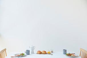 白い壁の前のダイニングテーブルに置かれた朝食セットの写真素材 [FYI02825005]