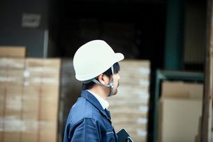 倉庫の前に立つ後ろ姿のヘルメットの男性の写真素材 [FYI02825016]