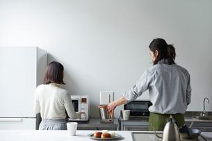 キッチンで会話しながら料理をする男女の写真素材 [FYI02825018]