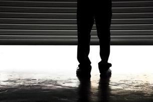シャッターの前に立つ男性の写真素材 [FYI02825026]