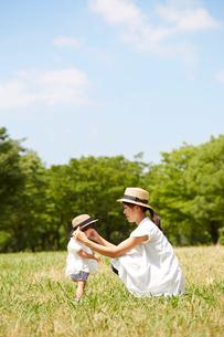 芝生の上でお揃いの帽子を被る母と娘の写真素材 [FYI02825033]