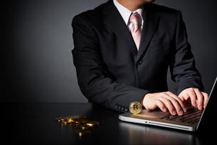 パソコンでビットコインのビジネスをするスーツを着た男性の写真素材 [FYI02825038]
