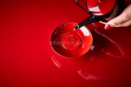 赤い天板で盃に注がれた屠蘇の写真素材 [FYI02825044]