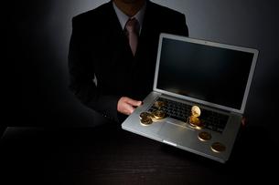 ビットコインとパソコンとスーツを着た男性の写真素材 [FYI02825152]