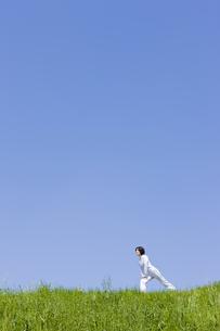 土手でストレッチする中年女性の写真素材 [FYI02825242]